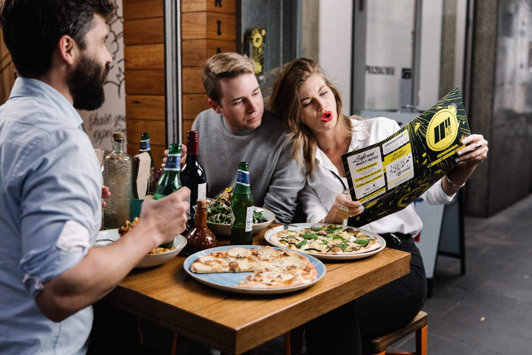 Customers sitting at a table at 11 Inch Pizza, looking at the menu